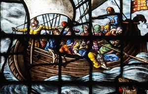 Stained glass window detail of boat in the Chapel at University College Oxford