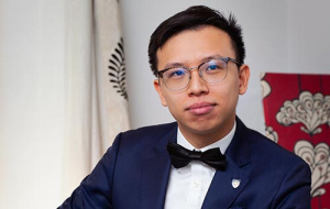 A picture of Baron Ho sharing experience of with college. He is wearing a suit, black bowtie and glasses. He has short black hair and a stoic look.