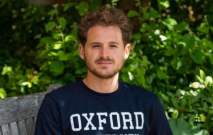 Ethan is sat on a wooden bench with foliage in the background. He is looking at the camera with a stoic expression, his hair is short, flowing, blonde curls and he has a cropped beard and is wearing a dark blue jumper.