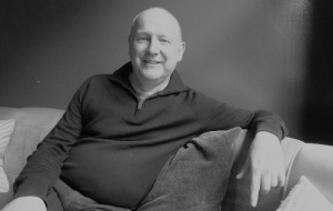Jonathan Hourigan sitting down on a sofa in black and white