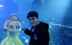 A picture of Xu standing in front of the mermaid statue with his thumbs up. He, with glasses and black hair, is wearing a black hoodie with black-and-white strips and blue logo. You can see many fishes swimming freely in the blue ocean behind.
