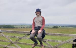 Alexander Walker sitting on a gate in an empty field