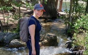 Dr Marina Filip on a hike in front of a river with a backpack on