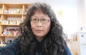 Jing Fang in front of pine bookshelf