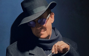 John Weltman in mysterious, dark lighting, dark grey costume complete with fedora in the guise of Truman Capote
