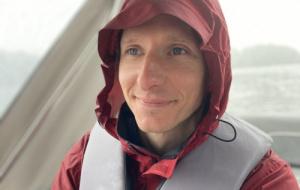 Professor Michael Barnes in red hooded parka in boat